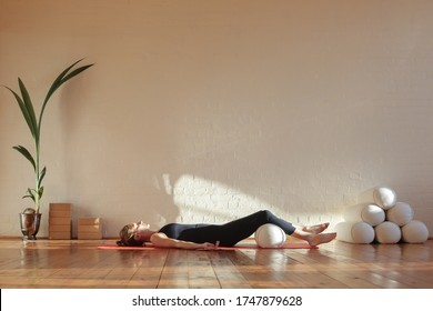 Young woman in corpse pose with knees resting on bolster doing breathing exercise at yoga session at home during self-isolation during corona virus