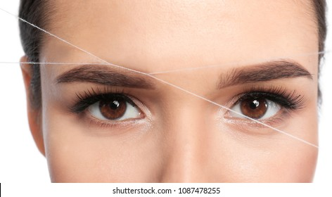 Young woman correcting eyebrow shape with thread, closeup