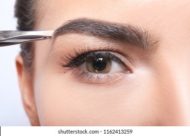 Young woman correcting eyebrow shape, closeup