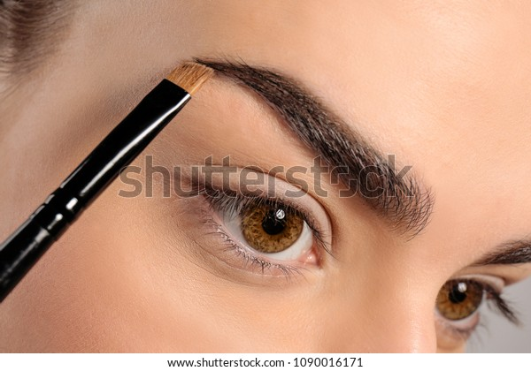 眉の形をブラシで修正する若い女性、接写