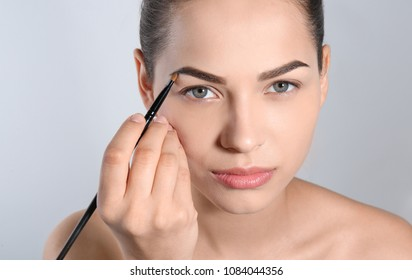 Young woman correcting shape of eyebrow with brush on light background