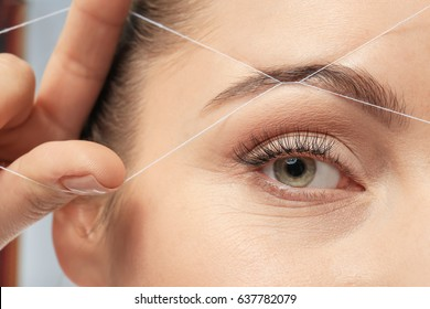 Young woman correcting shape of eyebrow with thread, closeup