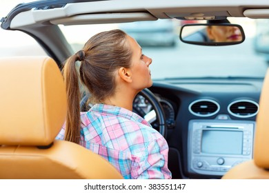 Young woman corrects makeup looking in the rearview mirror in a convertible
