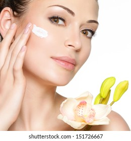 Young woman with cosmetic  cream on a clean fresh face. Healthy lifestyle concept