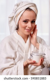 Young woman with cosmetic cream on a white background. Concept body care.