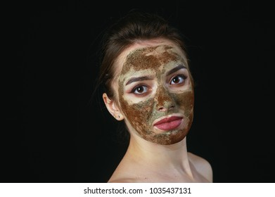 A young woman in a cosmetic mask on her face
