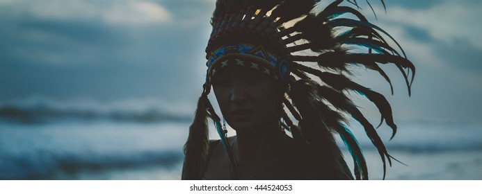 Young woman in costume of American Indian.woman portrait outdoors.Fashion young lady in the Indian roach.beautiful girl in a cap Indian.Indian feather hat. Girl on the beach in waves.girl hipster.
