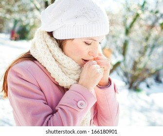Young woman woman coughing winter park