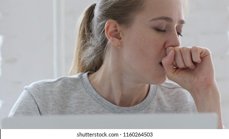 Young Woman Coughing at Work
