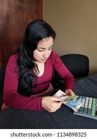 young woman counting mexican pesos banknotes