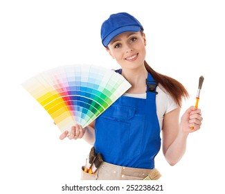 Young woman in  coverall with a color guide and paintbrushes on a white background.