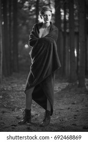 Young woman, covered in a blanket in a dark forest