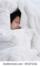 Young woman covered by blanket, sleeping