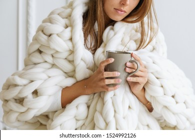 Young woman covered with chunky merino wool blanket on white background. Cozy winter style.