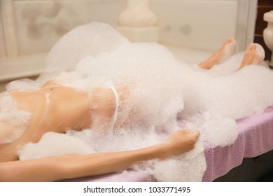 Young woman covered with foam in hammam