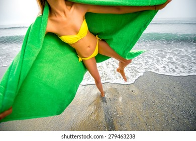 Young woman covered in green towel having fun on the beach