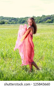 Young woman covered with red fabric walking on green valley