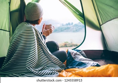 Young woman covered with warm plaid meets cold morning in sitting in a touristic camping tent with a cup of hot tea. Romantic camp traveling concept.