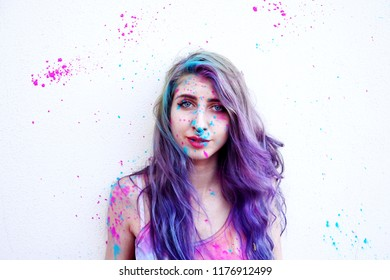 Young woman covering with drops of paint