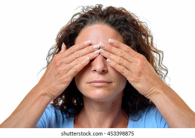 Young woman covering her eyes with her hands in a See No Evil concept, head and shoulders isolated on white