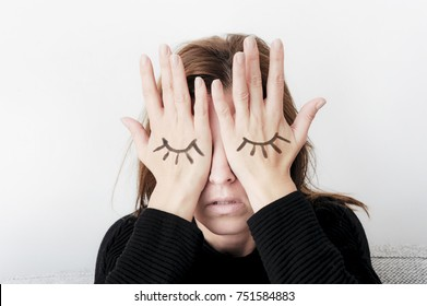 Young woman is covering her eyes with her palms. Eyes painted on her hand. Sorrow concept.