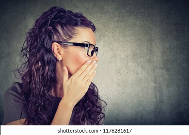 Young woman covering mouth while gossiping and telling secrets in whisper.