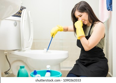 Young woman covering nose to avoid bad smell while cleaning a smelly toilet bowl