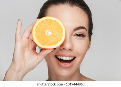 young woman covering one eye with half of orange isolated on white