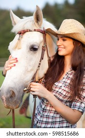 Young woman cowgirl holding caressing white horse