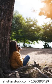 Young woman in a cozy sweater sitting under a tree and drinking hot tea at cup outdoors at sunset light with bokeh. Fall cozy.