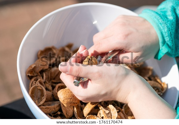 Young woman cracks nuts in a bowl