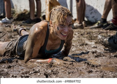 young woman crawling in the mud; participation in extreme sport, physical strength challenge