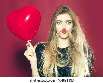Young woman with crazy face and heart balloon