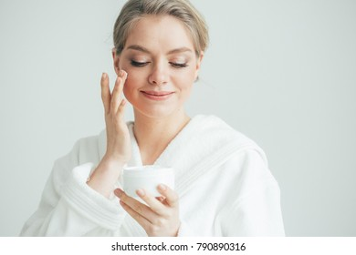 Young woman with cream face in bathrobe home