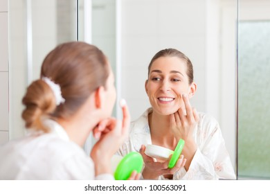 Young woman creams her face in front of a mirror to keep the skin smooth and soft