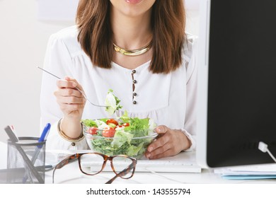 Young woman creative designer eating a salad in office. / Young businesswoman sitting from desk.