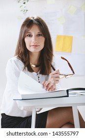 Young woman creative designer working in office. / Young businesswoman sitting from desk.