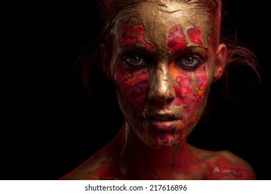 young woman with creative face-art and flow paint over black background