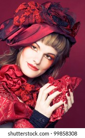 Young woman with creative make-up in red hat.