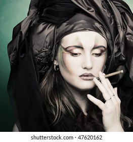 Young woman with creative make-up smoking cigarette