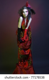 Young woman in creative vintage image in velvet dress and gloves