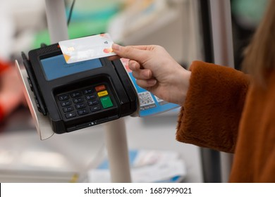 Young woman with a credit card pays for purchases at the checkout counter in the store