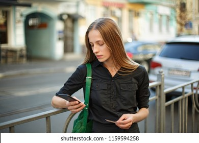 young woman with credit card and smartphone in hand on the background of old city street