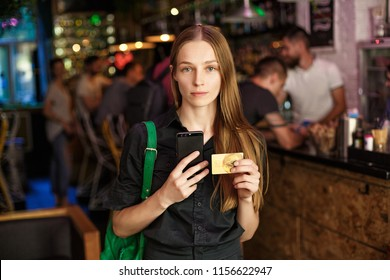 young woman with a credit card and stands in a cafe.