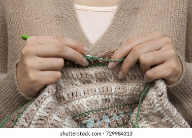 Young woman crochets a warm blanket with beige wool