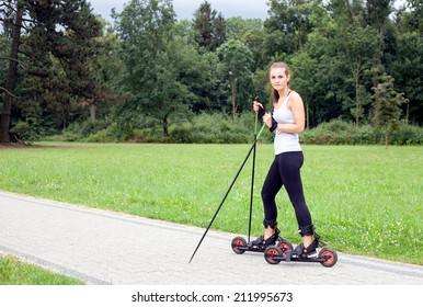 Young woman cross-country skiing with roller ski, park landscape