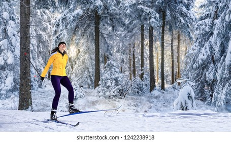 young woman cross-country skiing in the wintry forest