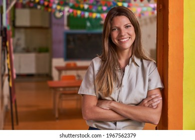 Young woman with crossed arms as a self-confident educator in preschool or daycare