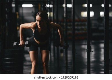 young woman at a crossfit style on dark gray background. Fitness, functional, training, and lifestyle concept