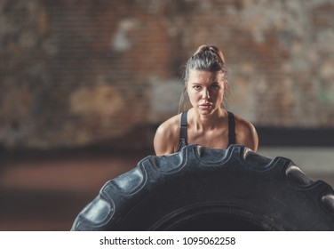 Young woman with a crossfit wheel indoors